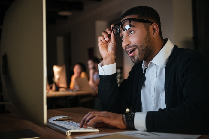 Shocked businessman working at night in office with computer