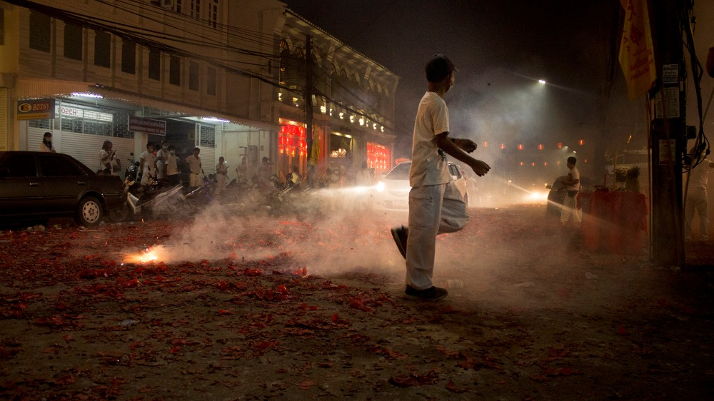 Kid kicks firecracker behind him at the Vegetarian Festival, Phuket